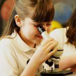 girl looking into microscope